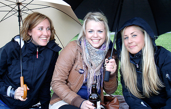 Emma, Jessica och Madde sitter glada men blöta och kalla under paraplyer.